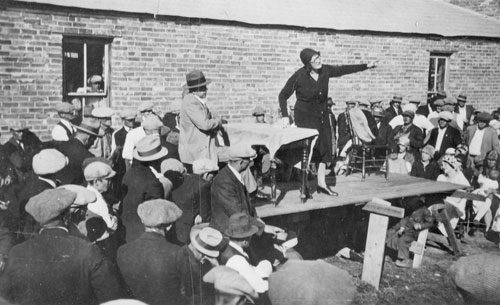 A woman stands on a table, addressing a crowd outside a low brick building.
