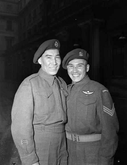 Two smiling young men wearing military uniforms and berets.
