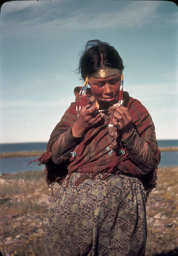 A young Inuit woman looks at a copper necklace in her grip. Behind her is a large body of water.