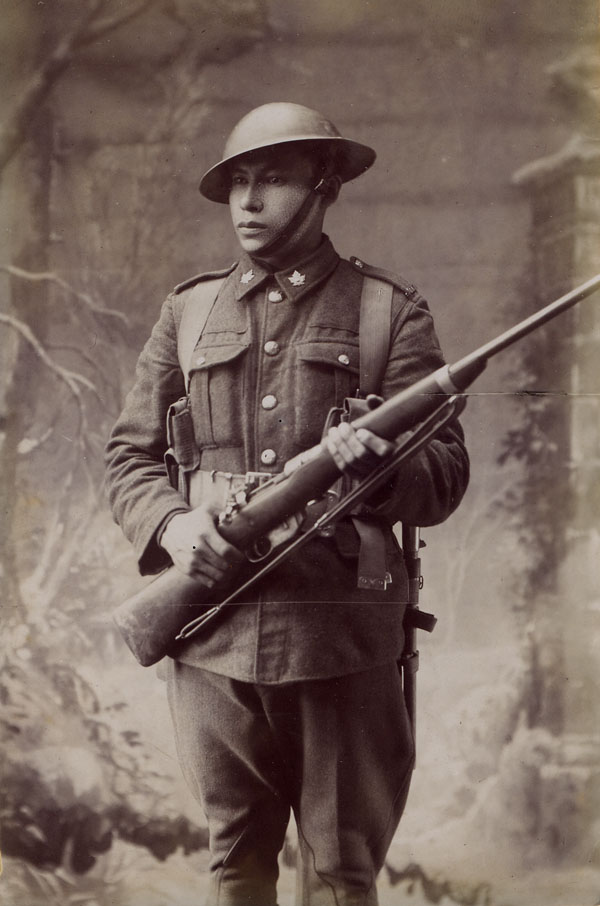 A young man wearing a uniform with maple leaves on the lapels bears a rifle, looking serious.