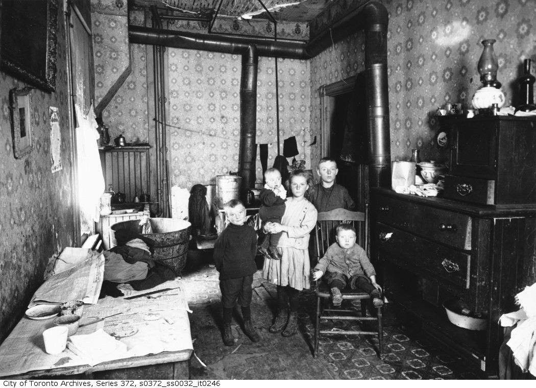 Five children pose in a room with a laundry line, a dresser, and a stove.