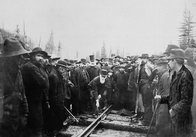 Railway workers stand around a man in a suit with a top hat who is hammering a spike into a railway.