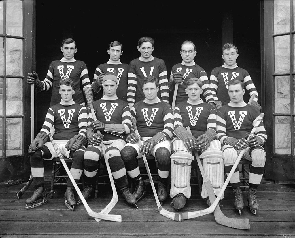 Ten men wearing hockey sweaters with a V and striped sleeves. They hold hockey sticks.