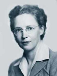 A headshot of a woman with glasses and a collared shirt looking intensely at the camera.