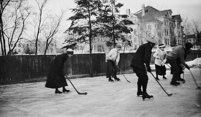 Men and women play ice hockey on a pond near a tall residential building.