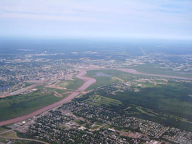 Aerial view of a city interspersed with fields of grass.
