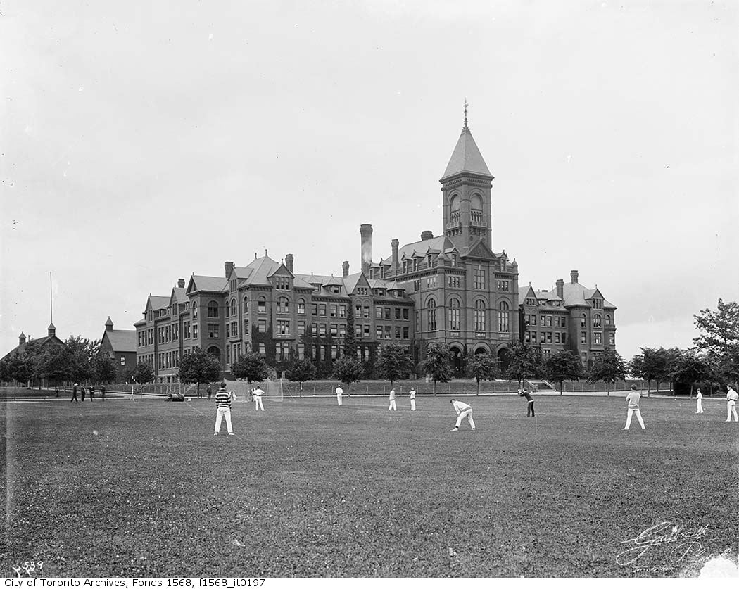 Young men play cricket outside of an ornate college building.