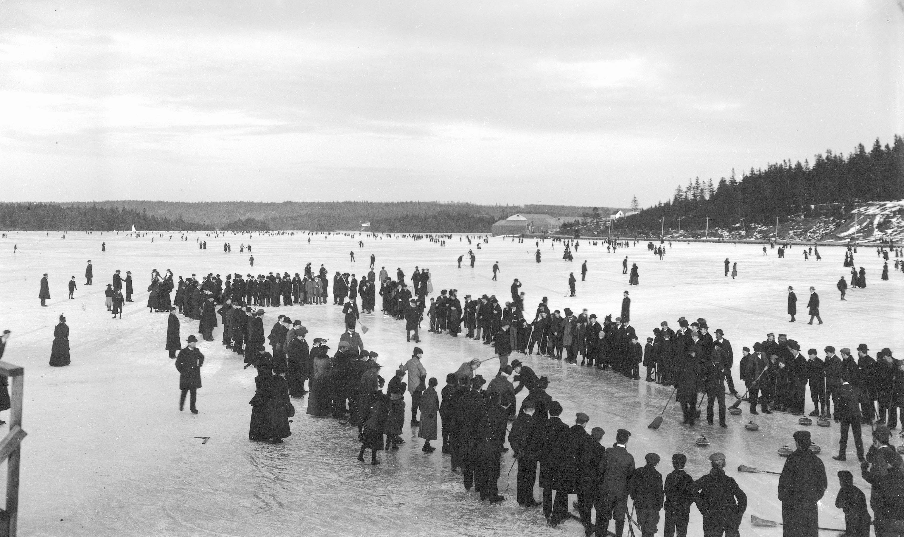 People line a curling rink on a frozen lake. People skate and play in the snow in the background.