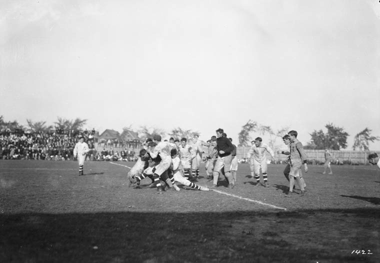 Men tackle each other and tussle on a football field.