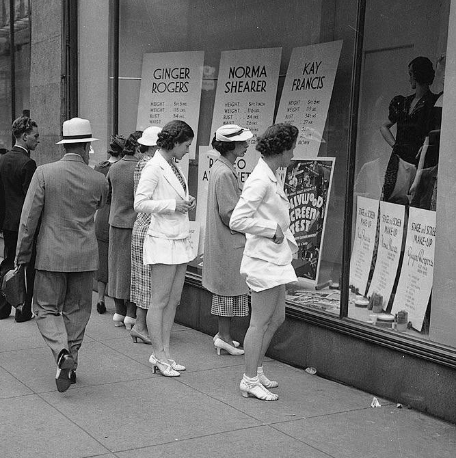 Women read the measurements of Ginger Rogers, Norma Shearer, and Kay Francis in store windows.