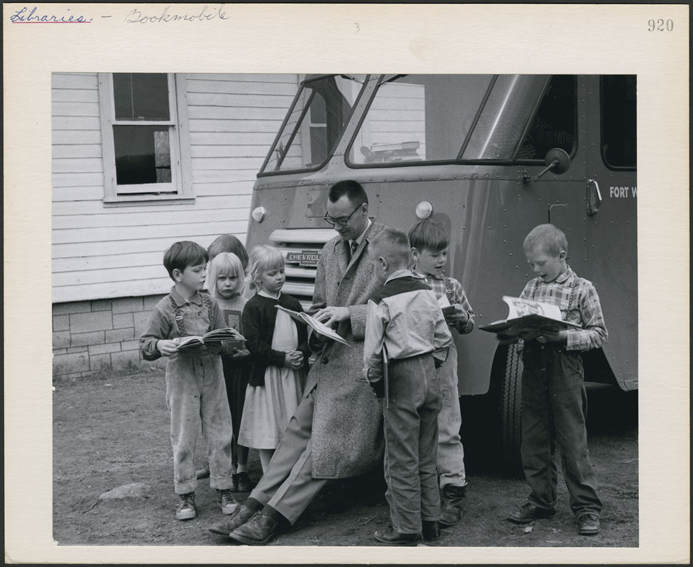 Kids gather around a man holding a book, leaning against the hood of a van. Some kids hold books.