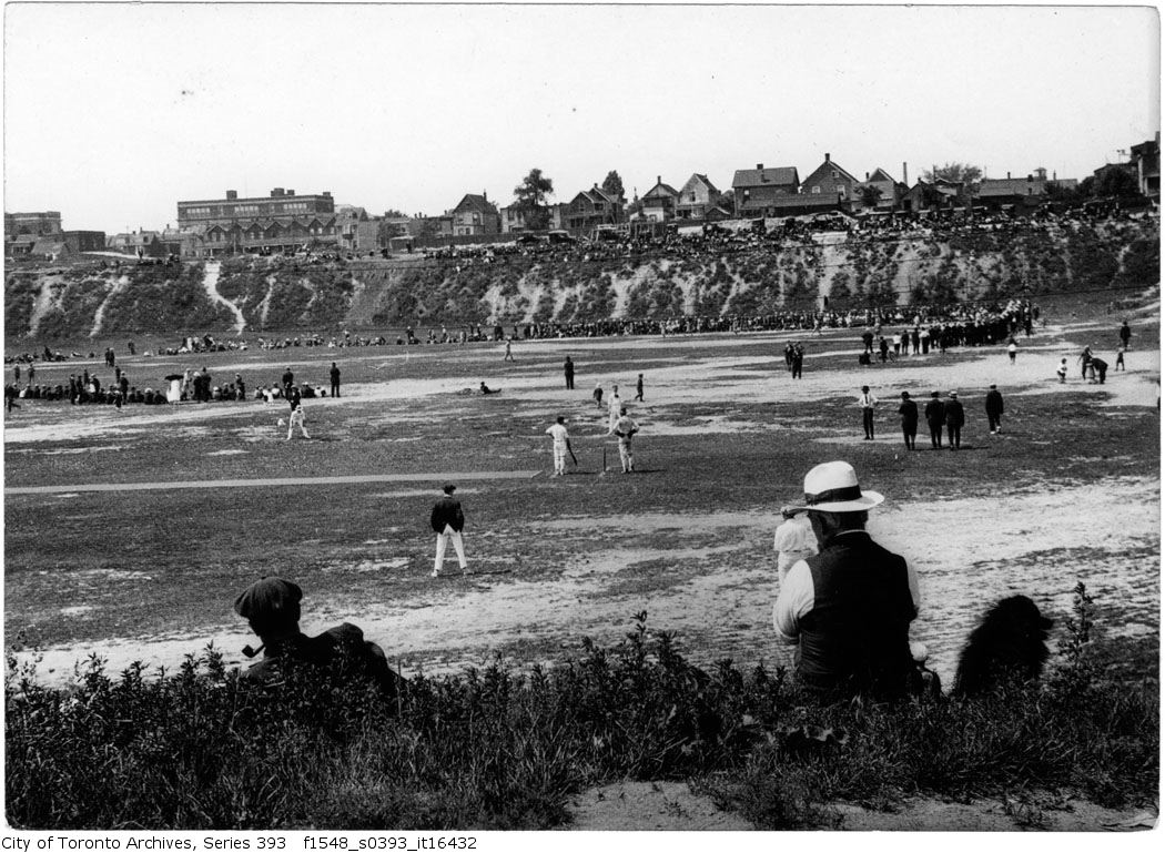Games of cricket and baseball occurring concurrently in a park. Spectators ring the field.