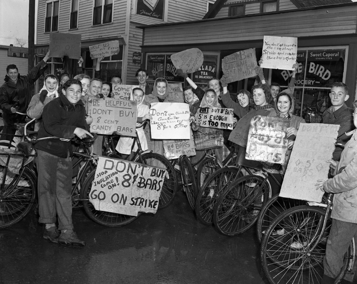 A crowd of children with their bikes, holding signs protesting 8-cent candy bars.