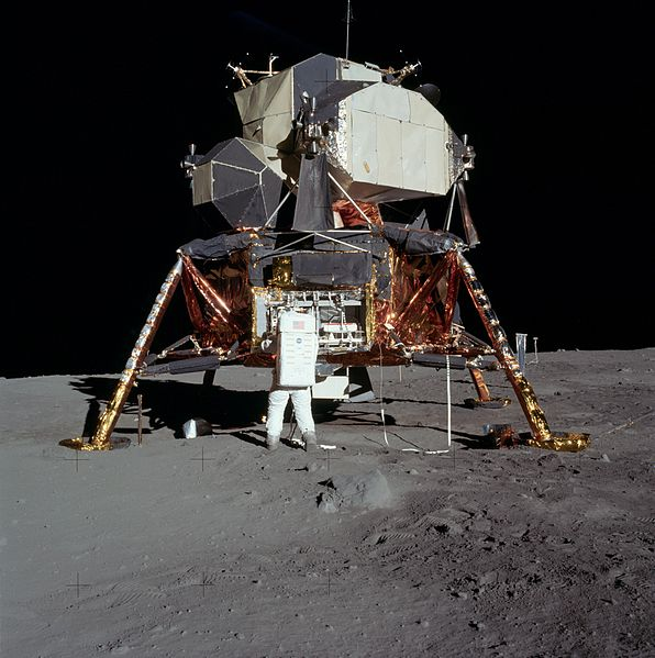 A spacecraft with legs and a metal capsule. An astronaut stands in front of it.