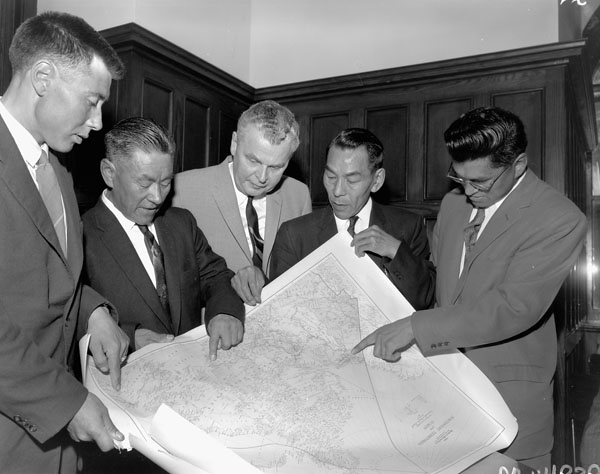 Five men in suits hold a map and point at it.