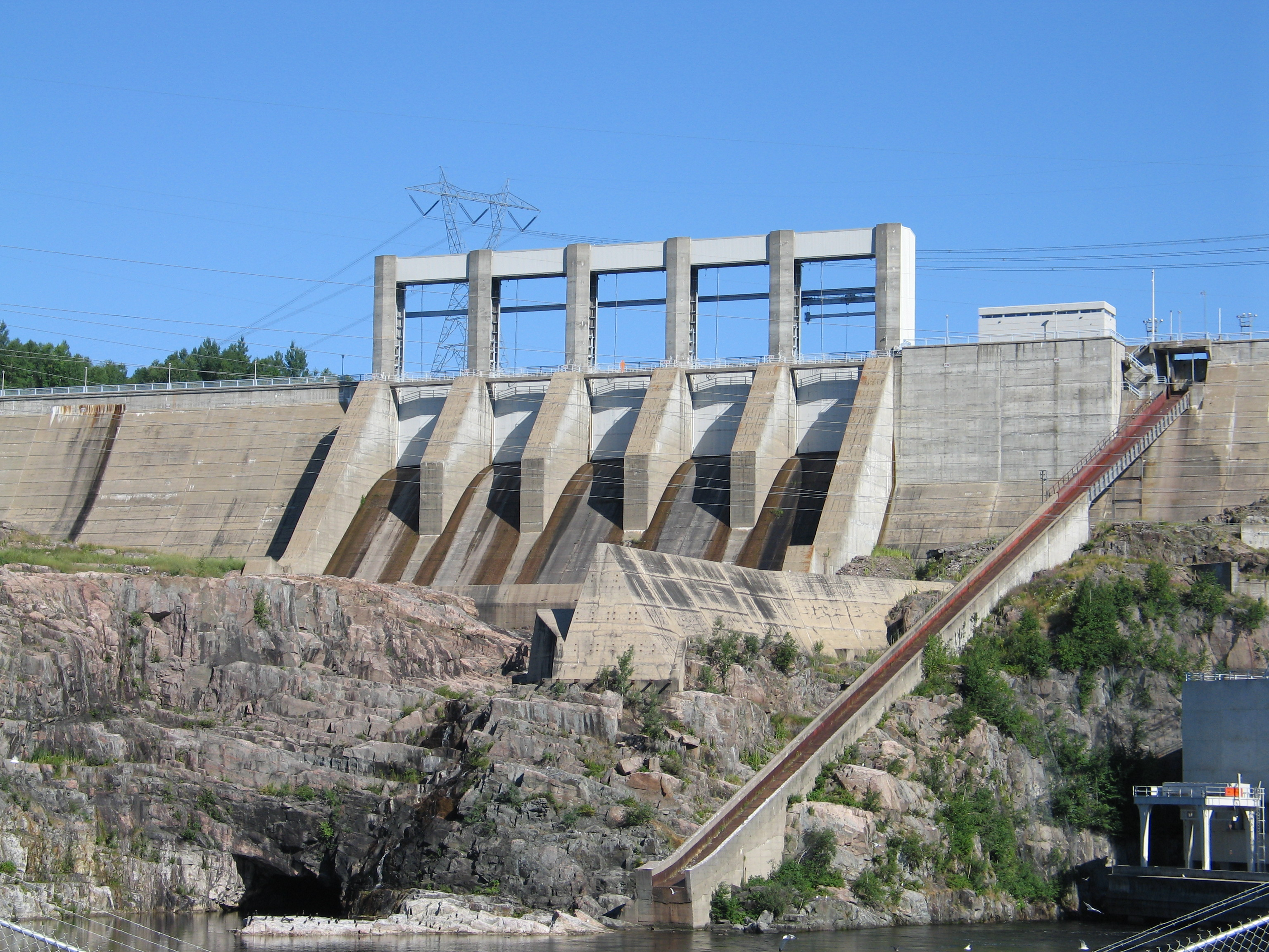 A concrete generating station sits above a river.
