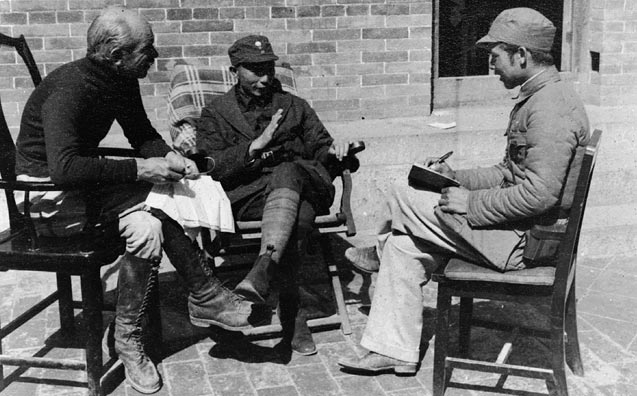 Three men sit and talk on mismatched chairs on a stone patio.