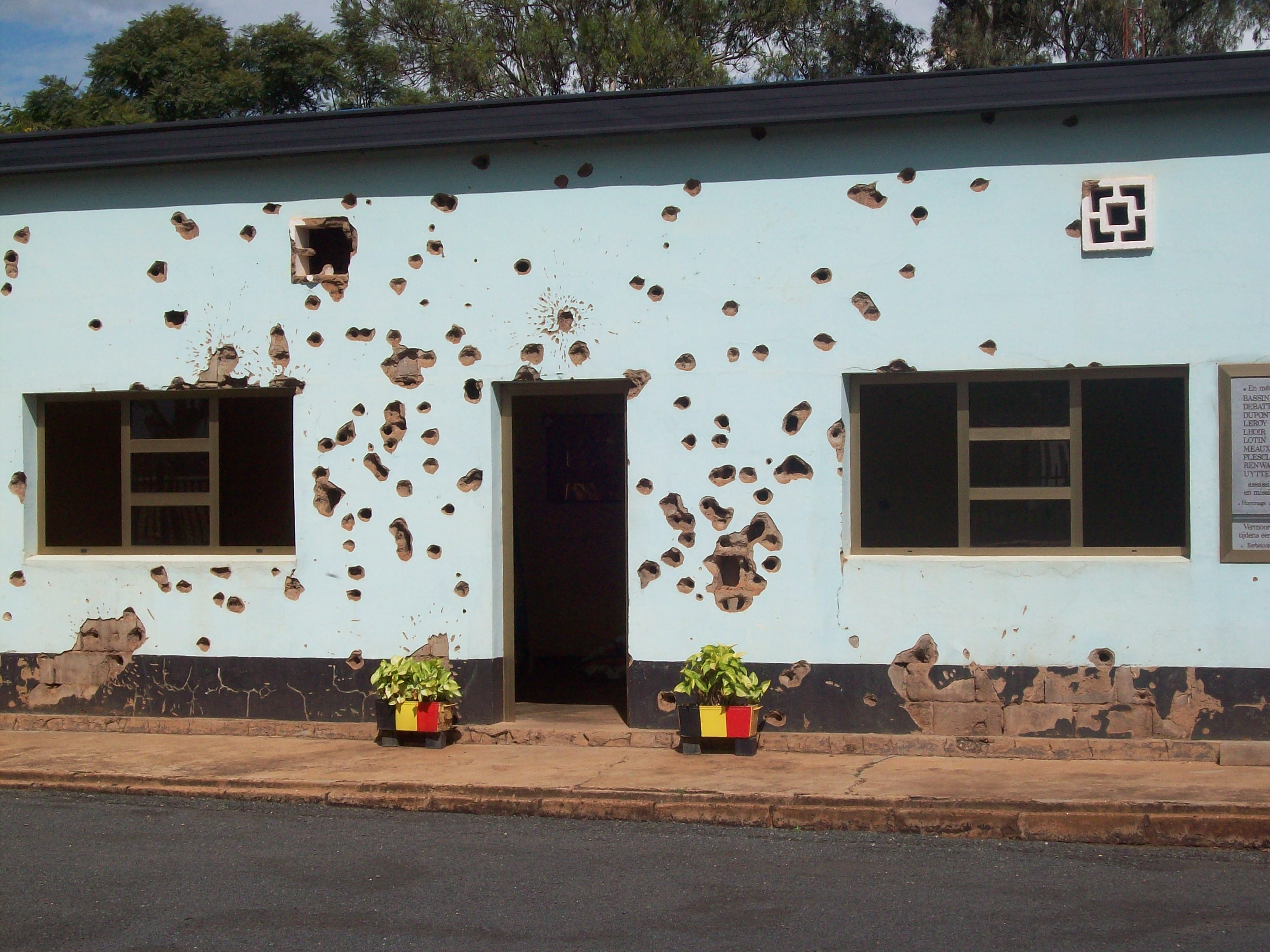 A small building riddled with bullet holes. Two potted plants outside the door bear Belgian colours.