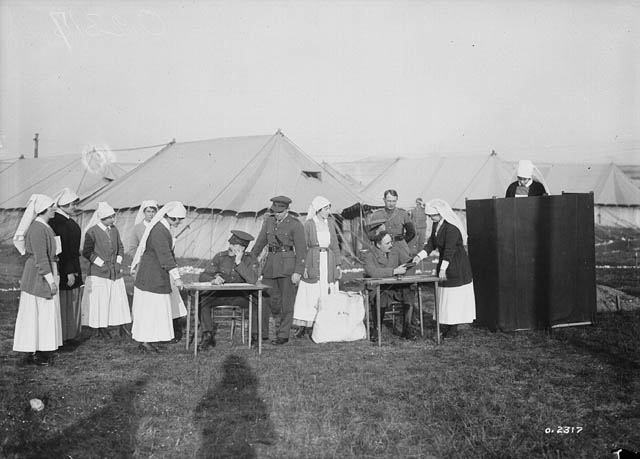 Several nurses gather around tables manned by officers; one is in a voting booth. Behind are tents.