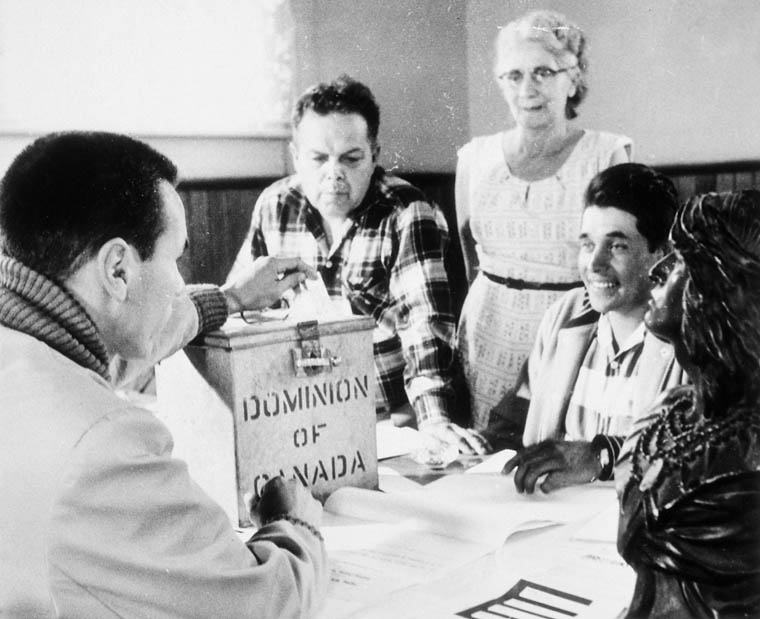 Three men and a woman are gathered around a Dominion of Canada ballot box.