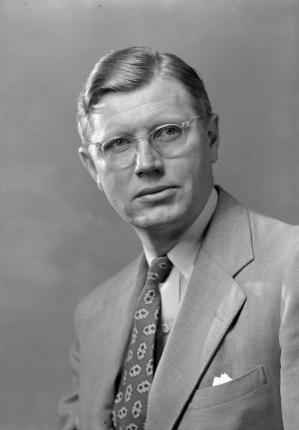 Close-up of a man in a suit with a patterned tie and clear-rimmed glasses.