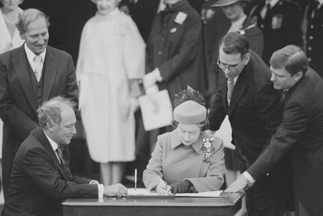 A woman and a man seated at a small table sign a document.
