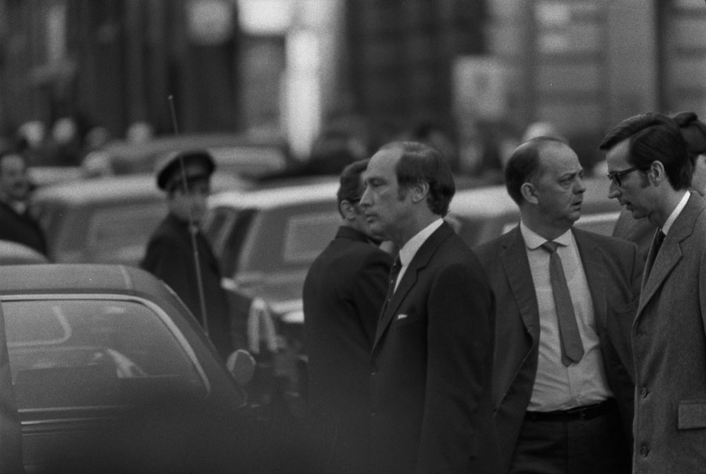Two men in suits walk behind a sea of cars, looking solemn.