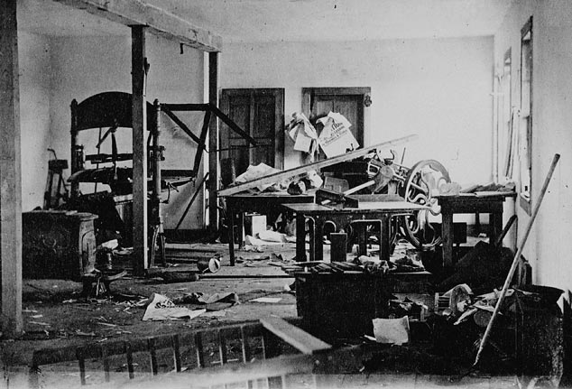Printing presses have been destroyed in a ransacked room.