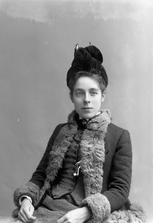 Photo portrait of a woman wearing a fur-lined coat and a velvet hat.