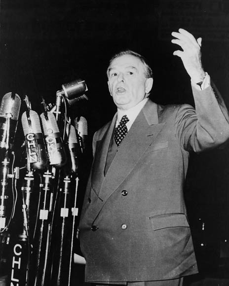A middle-aged man in a suit gestures while speaking into several microphones.