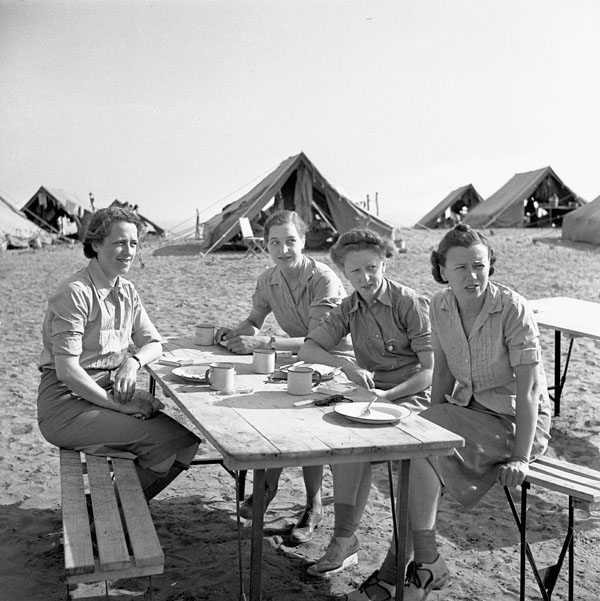Four women sit at a wooden table in a desert. Several large tents are in the background.
