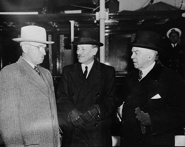 Three men in overcoats and formal hats stand on a ship's deck.