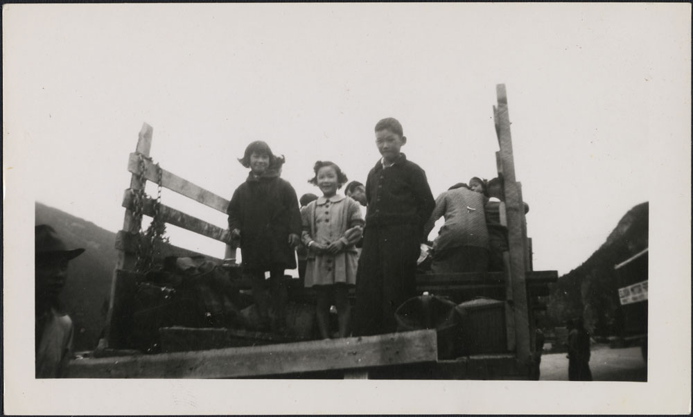 Two young girls and a boy stand in the back of a pick-up truck.