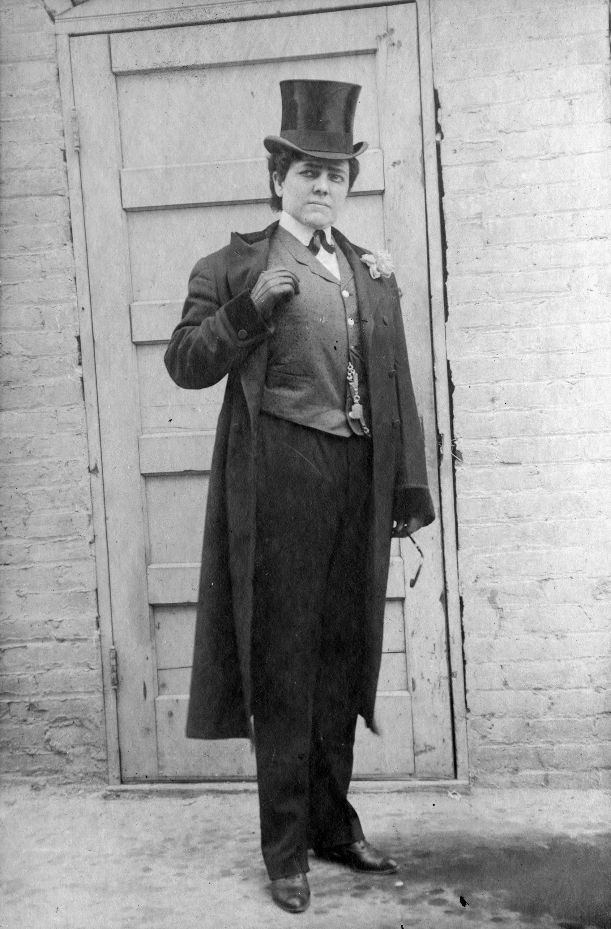 A woman in a top hat and tails poses in front of a door.