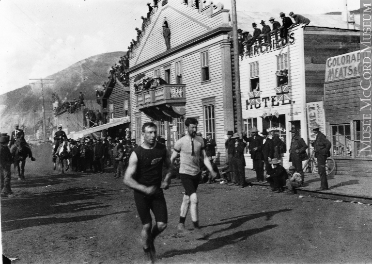 Two men run past a crowd gathered outside simple storefronts.