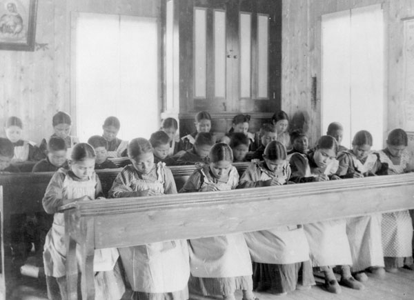 Girls and boys sit at long desks, heads bent over their schoolwork.