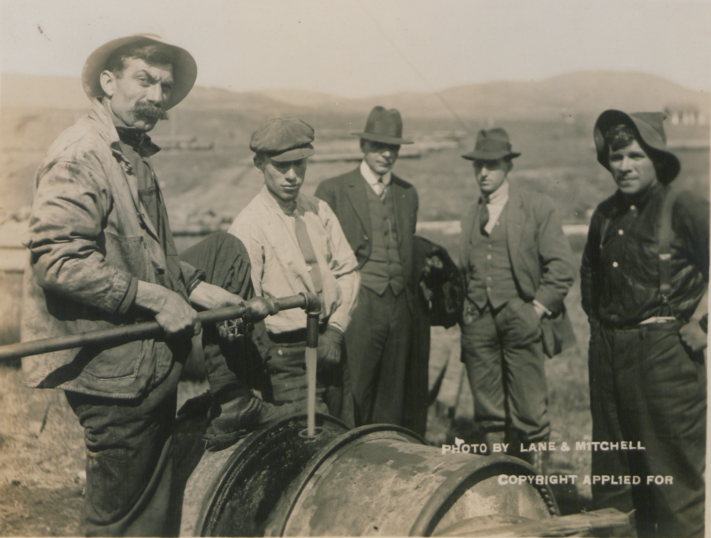 A man feeds oil into a drum using a pipe. Four other men (two working, two in suits) look on.