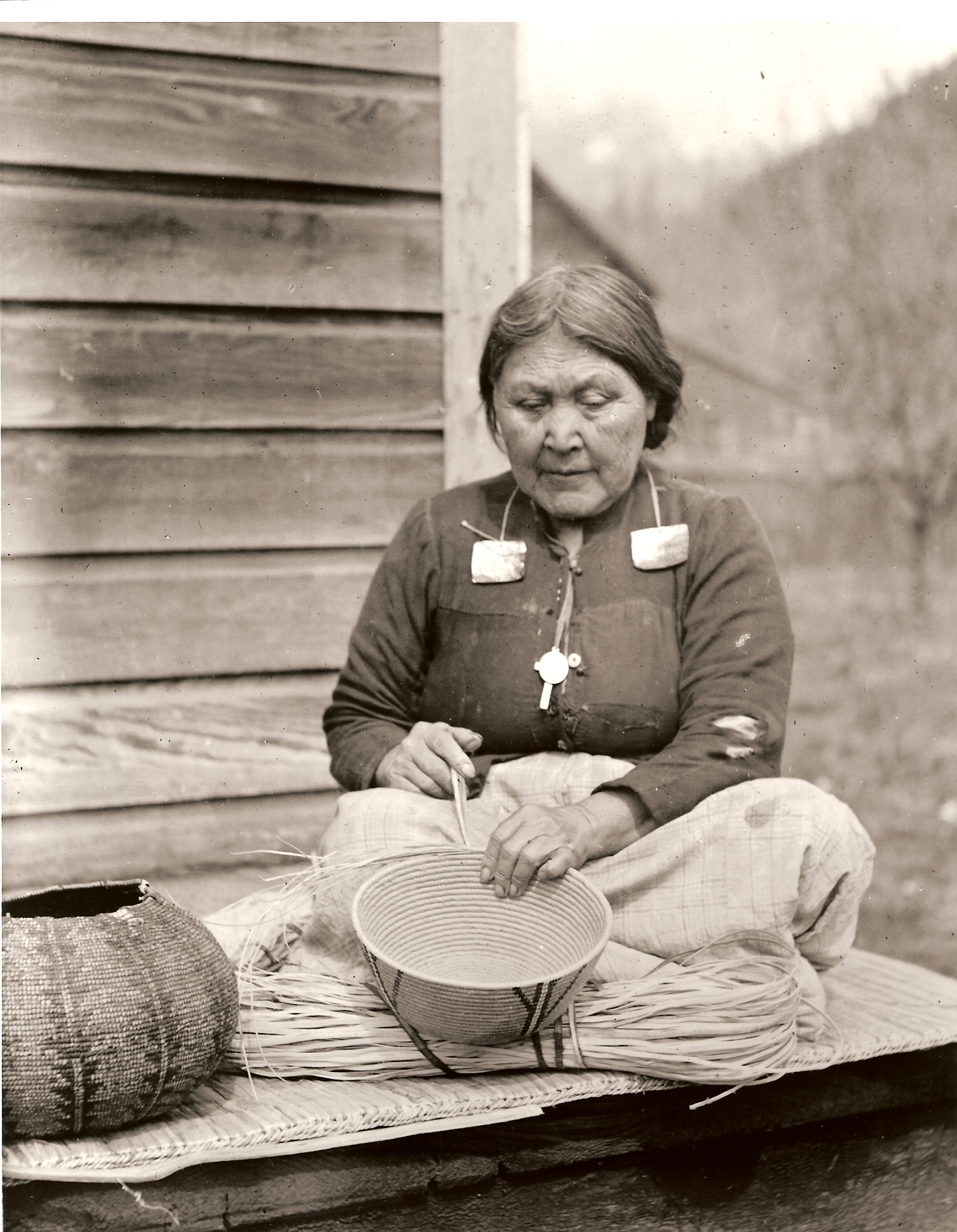 An older woman sitting on a porch weaves a basket.