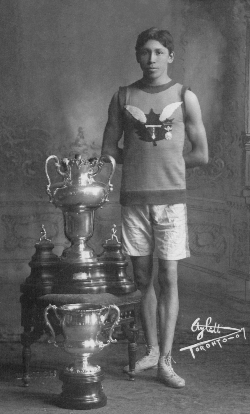 A young man poses beside two large trophies. He wears shorts, a tank top, and running shoes.