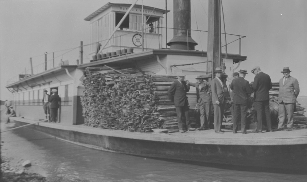 A steamer ship with a dozen men in suits and a large pile of lumber on the deck.