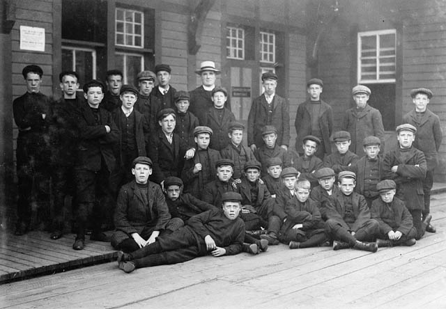 Thirty boys pose outside of a wooden building.