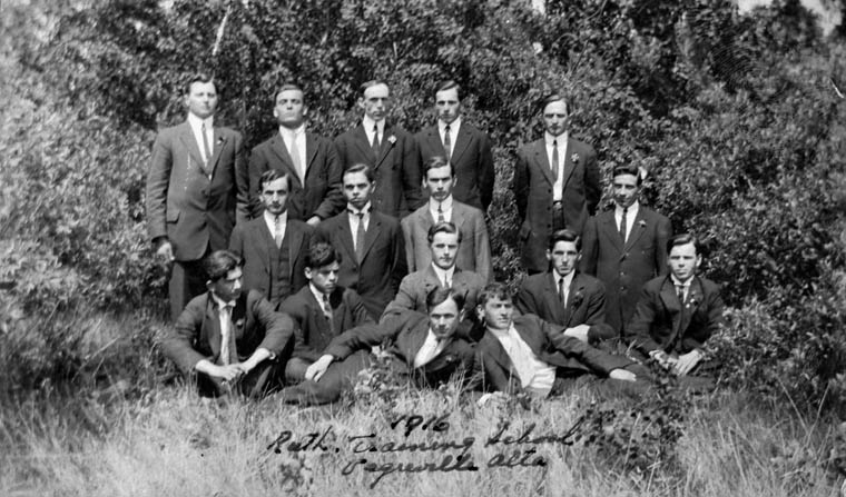 Sixteen young men in suits pose outdoors on grass in front of foliage.