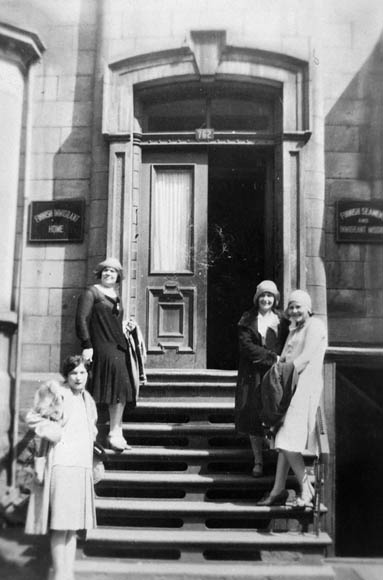 Four young women pose on the steps of a brownstone.