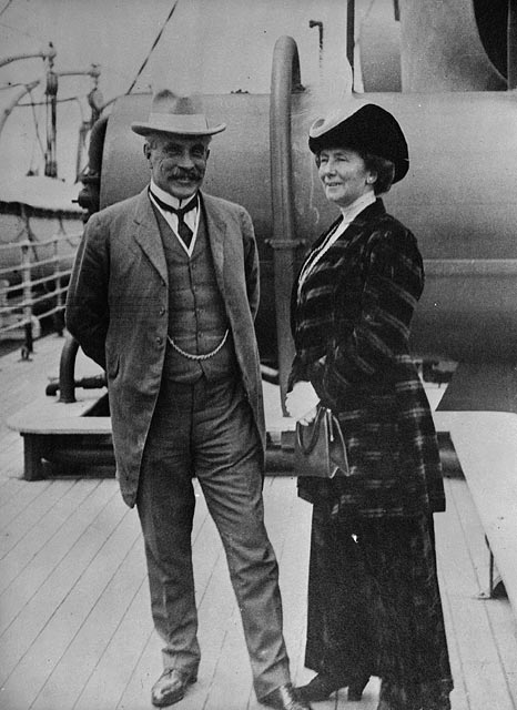 An older man in a suit and an older woman in a long dress stand on a ship deck.
