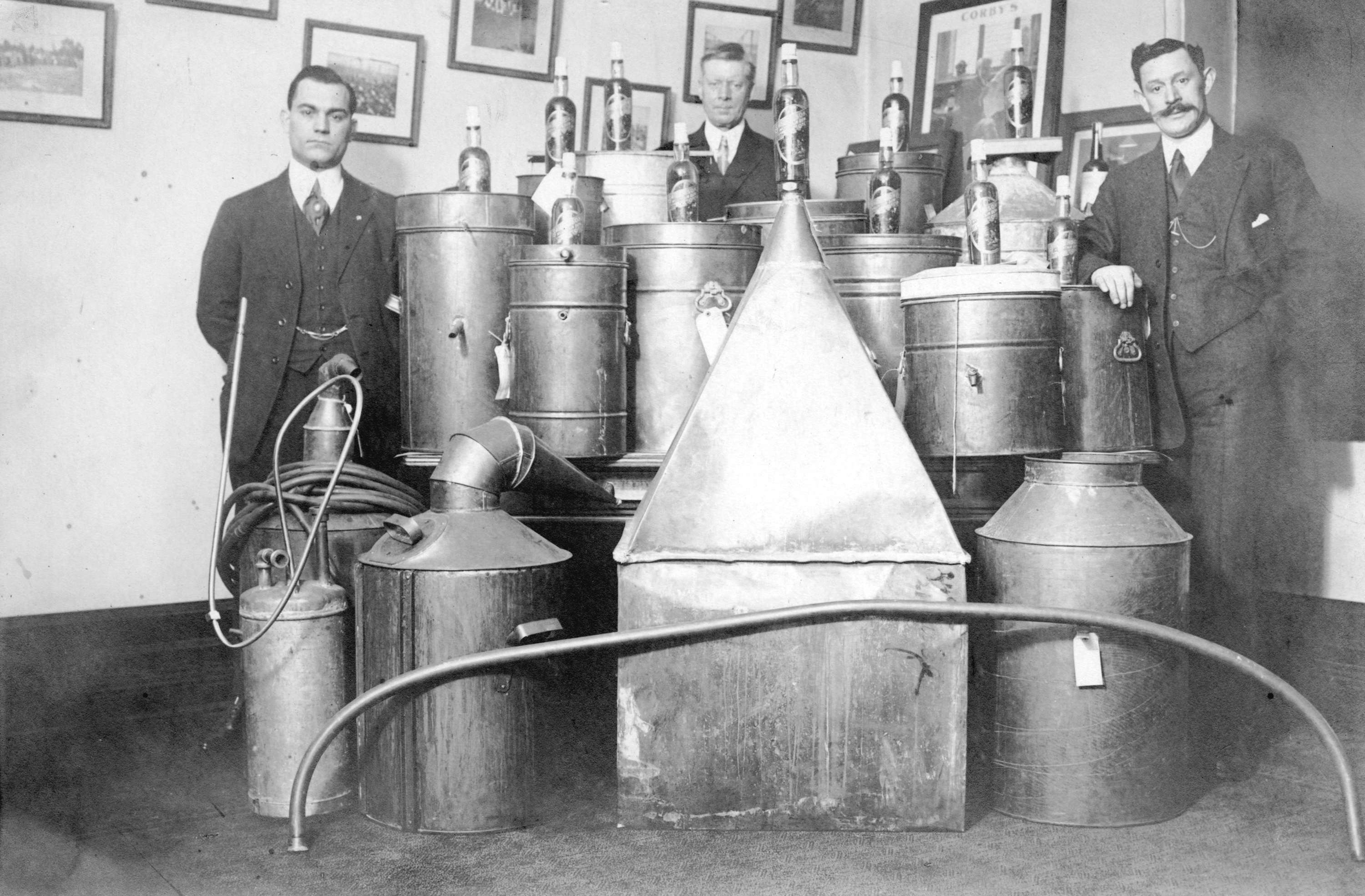 Three men pose with a dozen metal stills.