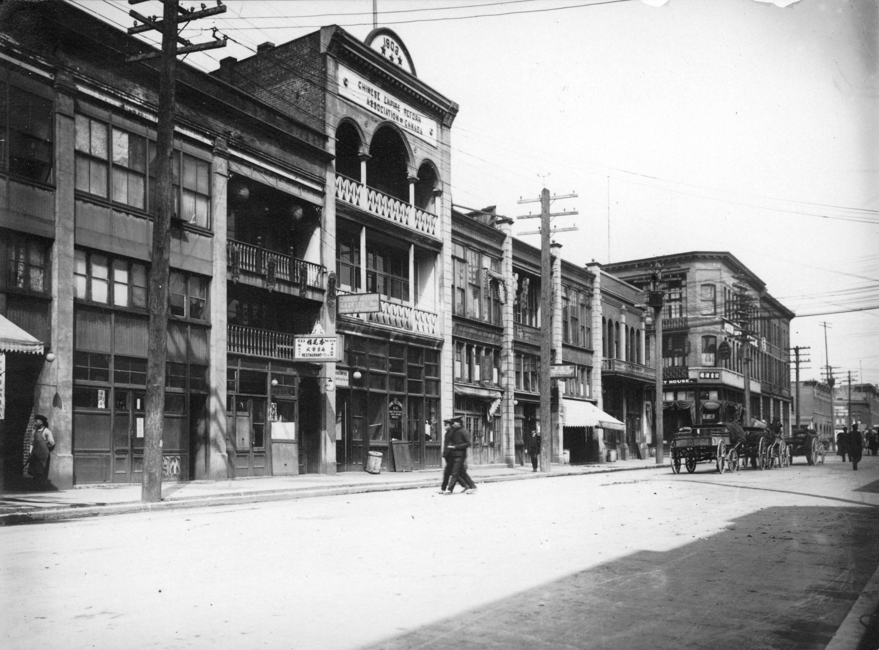 A city street in 1907. A few carriages and pedestrians go down the street past storefronts.