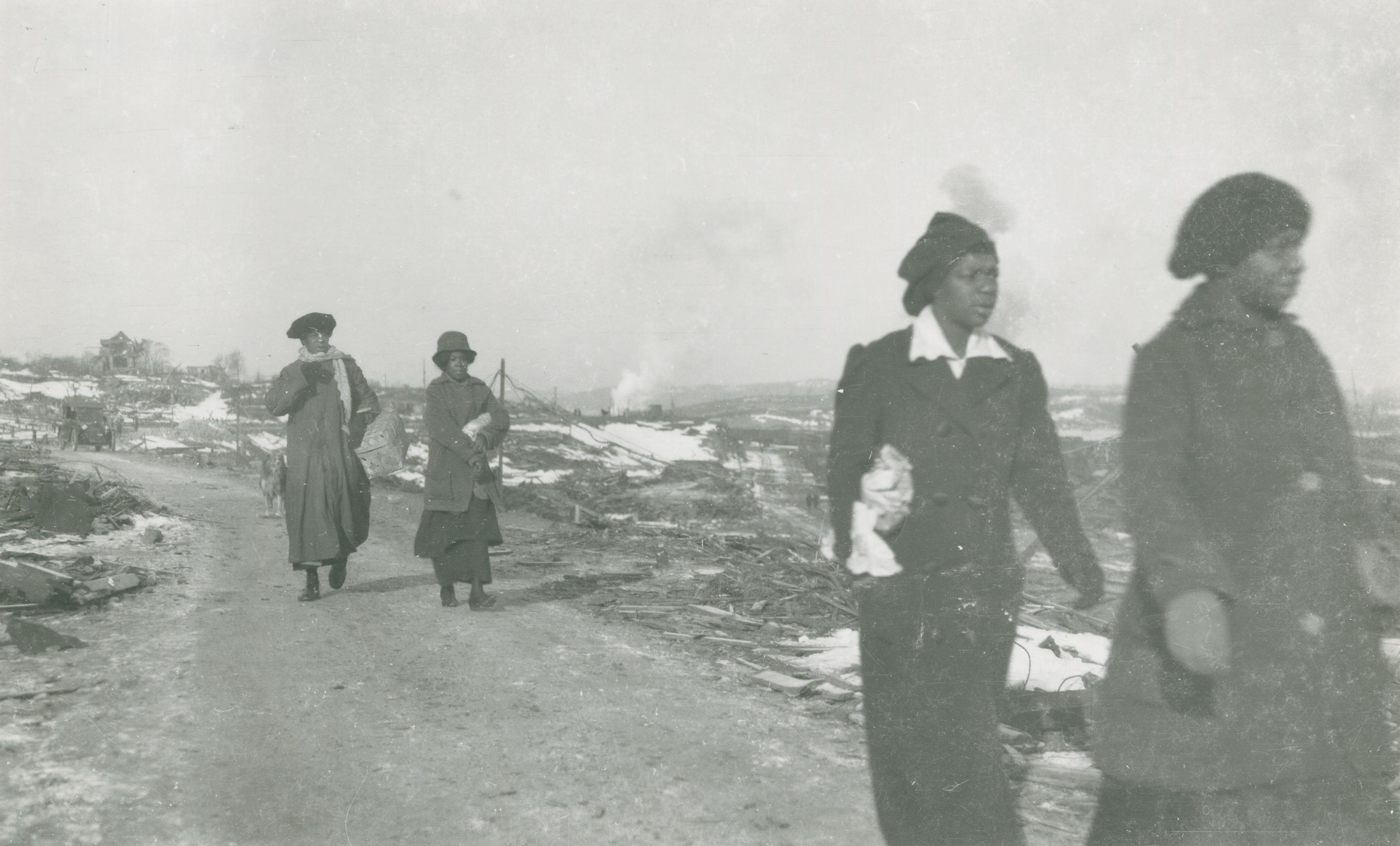 Four Black women in overcoats walk down a dirt road that runs through barren land.