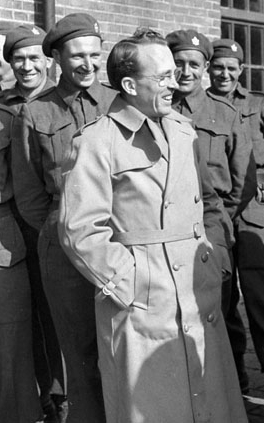 A man in a trench coat smiles and laughs. Smiling soldiers stand in the background.