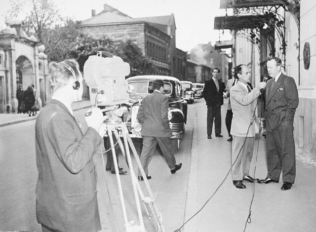 A TV camera is pointed at a man interviewing another man. A couple of men look on.