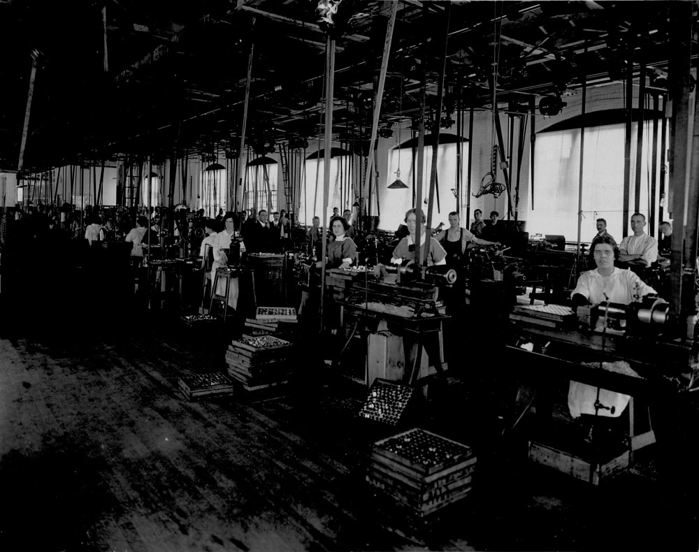 Women and men in war production in a factory.